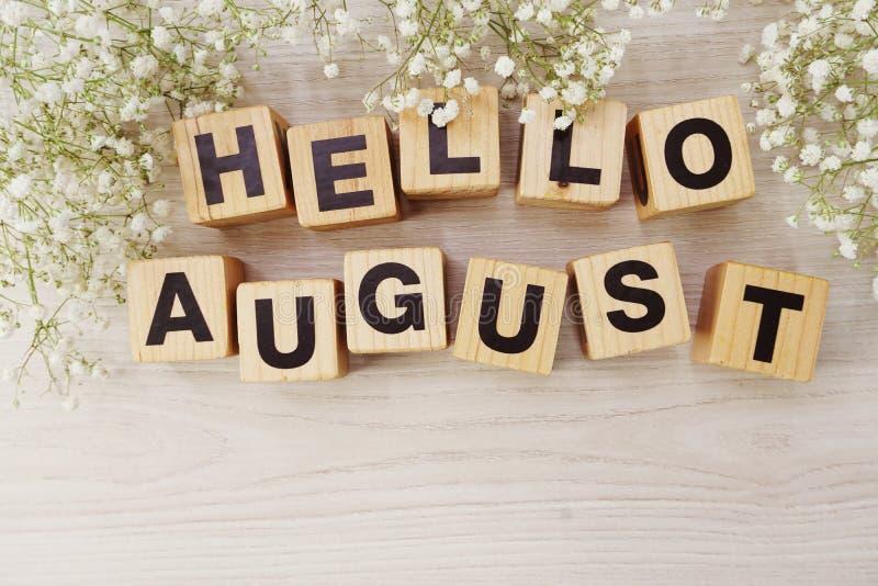 Hello august alfabetbokstäver på träbakgrund royaltyfri bild