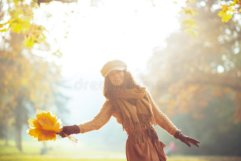 Cheerful woman with yellow leaves outside in autumn park royalty free stock photo