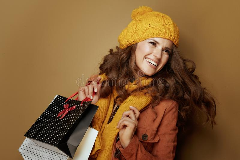Cheerful stylish woman shopper  on brown background stock photos