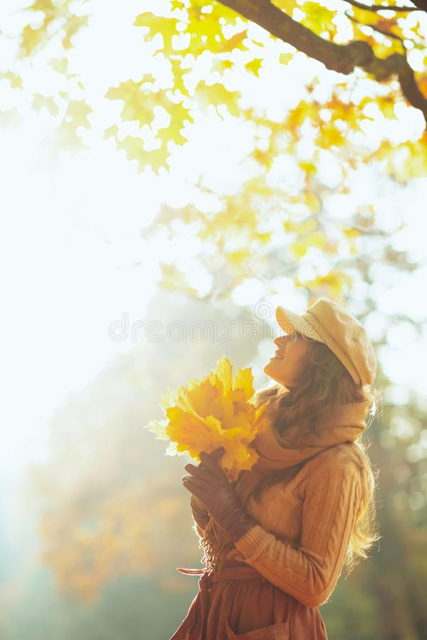 Happy woman with yellow leaves looking up at copy space royalty free stock image
