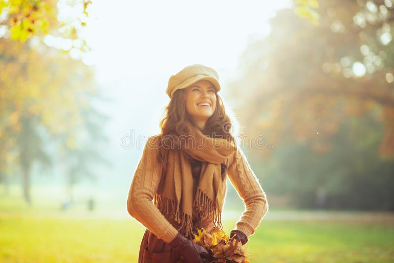 Woman outside in autumn park throwing up pile of yellow leaves stock image