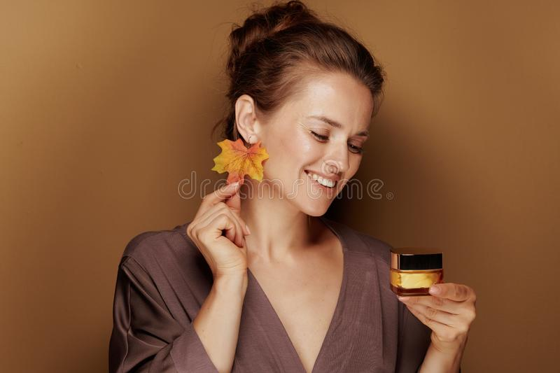 Happy woman with autumn leaf earring looking at facial creme stock photography