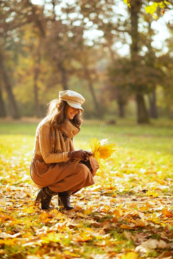 Happy young woman outdoors in autumn park gathering leaves royalty free stock images