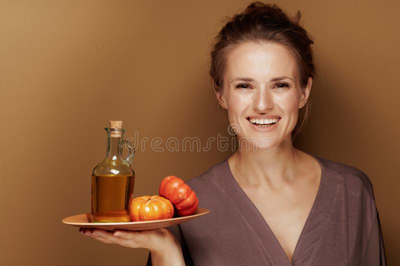 40 year old woman showing pumpkin oil against bronze background stock images