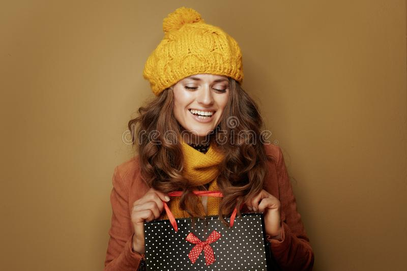 Happy woman with black dotted shopping bag on brown background royalty free stock photo