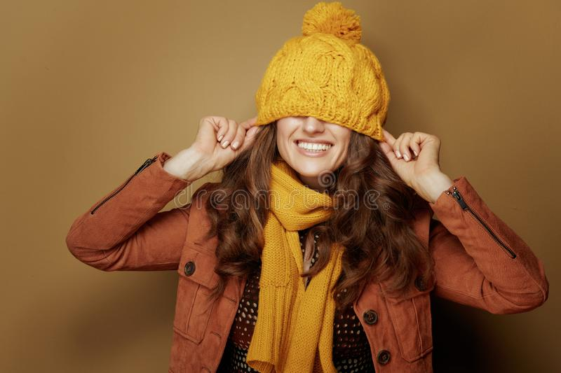 Happy woman with beret over eyes against beige background. Hello autumn. Portrait of happy trendy woman in yellow scarf with beret over eyes against beige royalty free stock images