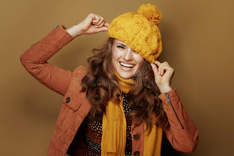 Smiling woman playing with beret against brown background royalty free stock images