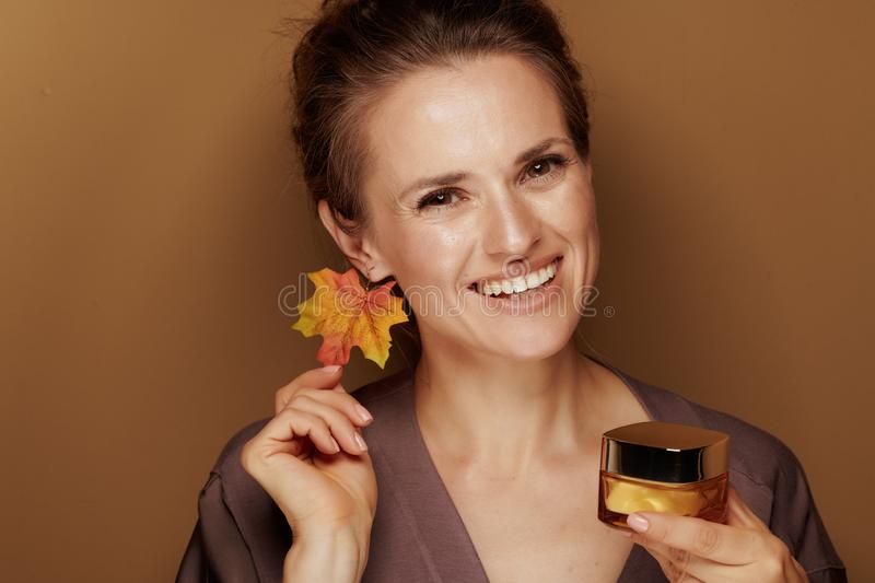 Smiling woman with autumn leaf earring showing facial creme royalty free stock image