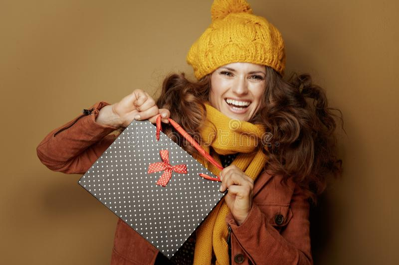 Smiling young woman showing black dotted shopping bag royalty free stock photography