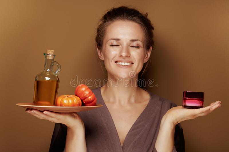 Relaxed 40 year old woman with pumpkin oil and facial creme. Hello autumn. relaxed modern 40 year old woman in a bathrobe with pumpkin oil and facial creme on stock image