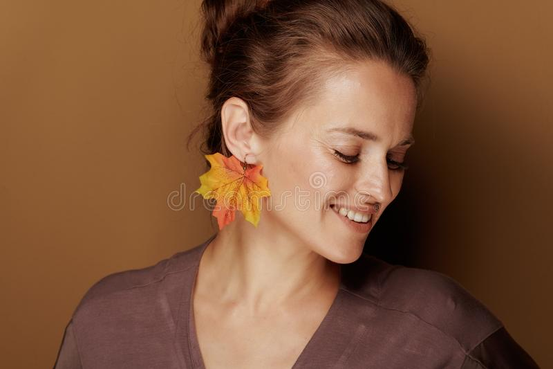 40 year old woman with autumn leaf earring on brown background stock photos