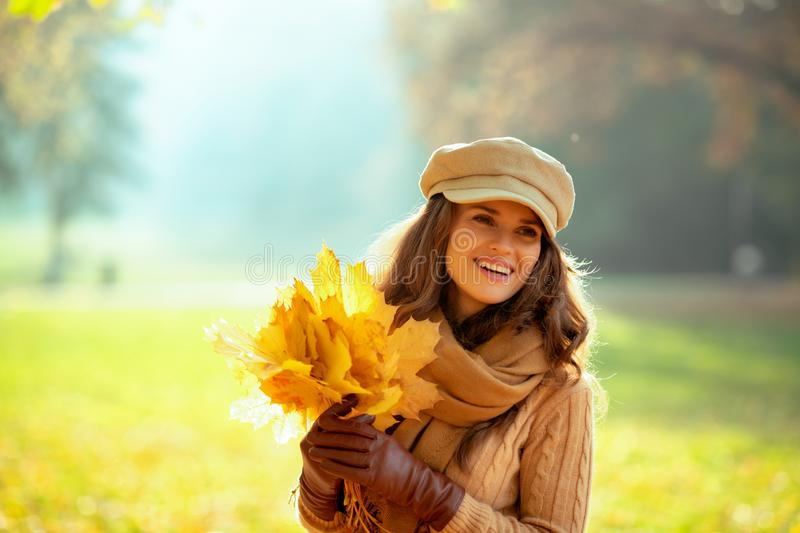 Woman with yellow leaves looking aside outdoors in autumn park stock photos