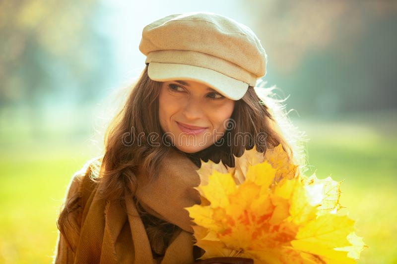 Woman with yellow leaves looking aside outside in autumn park royalty free stock images