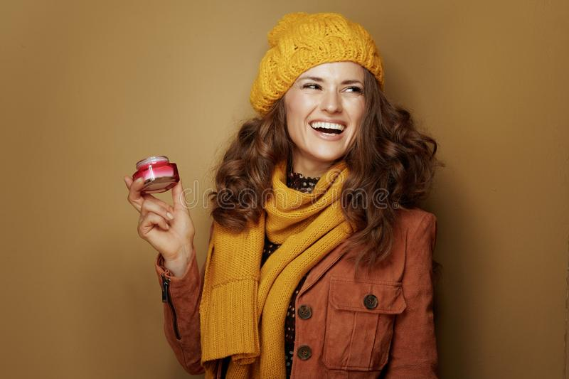 Smiling woman with jar of facial creme looking at copy space royalty free stock images