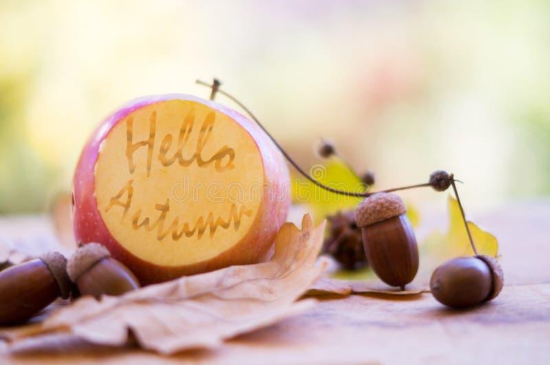 Hello autumn text on a cut apple stock image