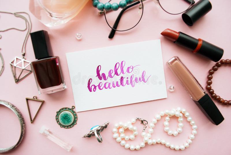 Hello beautiful handwritten with watercolor in calligraphy style. Women`s fashion accessories arrangement on a pink pastel backgr royalty free stock photo