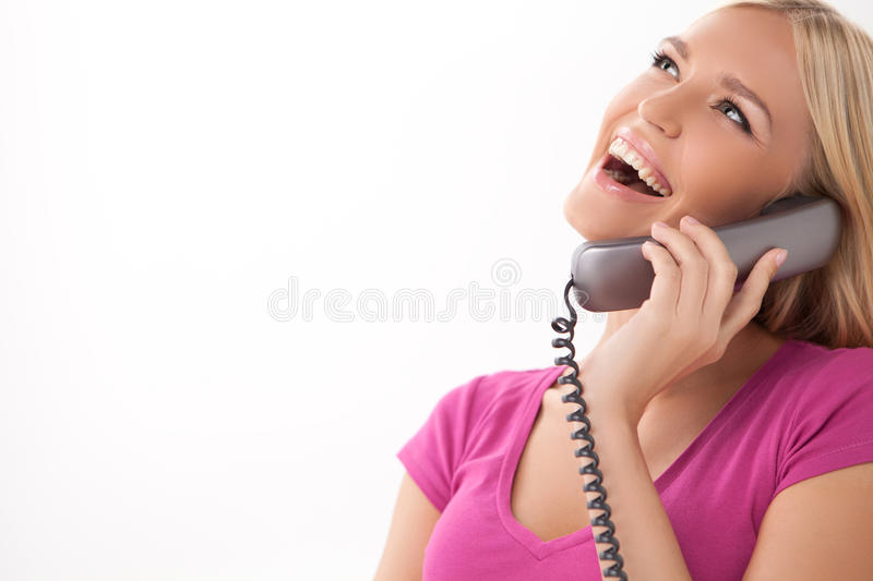 Hello! Beautiful young women talking at phone and smiling while royalty free stock photos