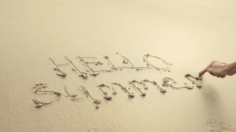 HELLO-de ZOMER op het strandzand wordt door golven altijd wordt gewassen geschreven die royalty-vrije stock foto's