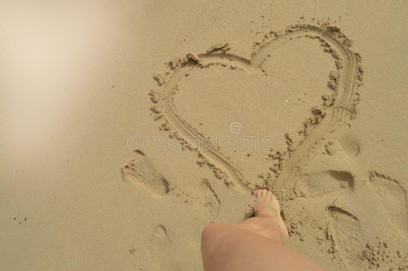Hello-de zomer, de voeten van vrouwen trekt een hartteken op het natte zand terwijl status op het zandige strand Concept rust, on stock afbeelding