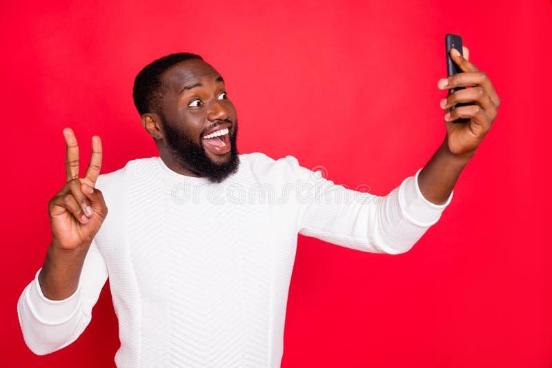 Hello dear followers. Photo of funny dark skin man holding telephone making selfies showing v-sign symbol wear white. Hello dear followers. Photo of funny dark stock photo