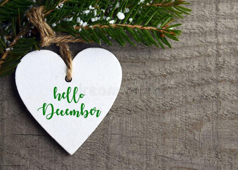 Hello December.Decorative white wooden Christmas heart and fir tree branch on old wooden background. royalty free stock image