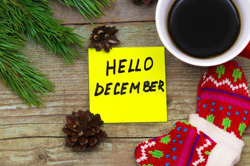 Hello December- handwriting in black ink on a sticky note with stock image