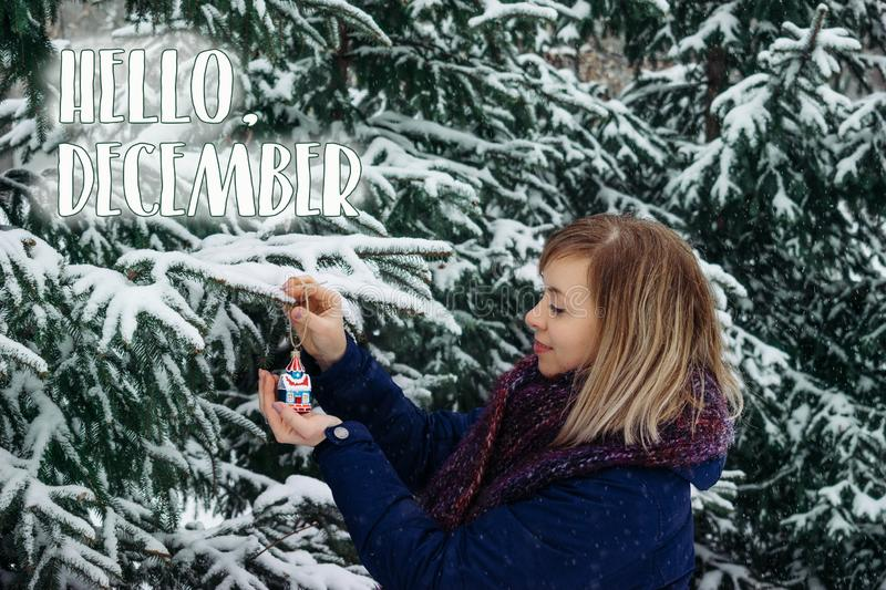 Hello, December. Outdoor winter Christmas portrait of Woman in snowy forest. Smiling Caucasian blonde woman decorates fir tree for. The holiday under the royalty free stock photos