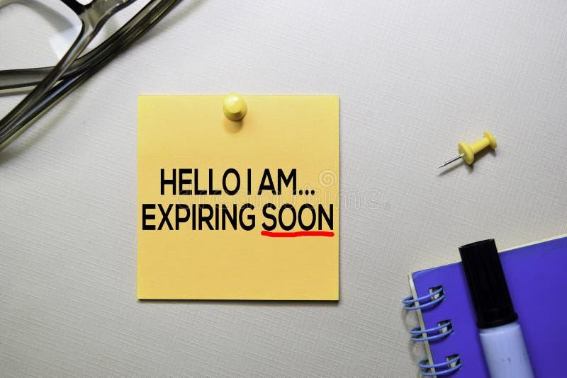 Hello förfaller jag snart text på klibbiga anmärkningar som isoleras på kontorsskrivbordet arkivbilder