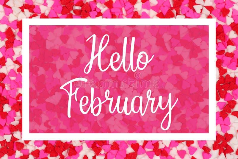 Hello Februari hälsningkort med vit text över en godishjärtabakgrund royaltyfri foto