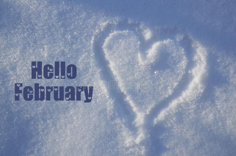 Hello February greeting card with heart drawing on natural white snow on a sunny day.Winter season or Valentines Day concept. Selective focus stock image