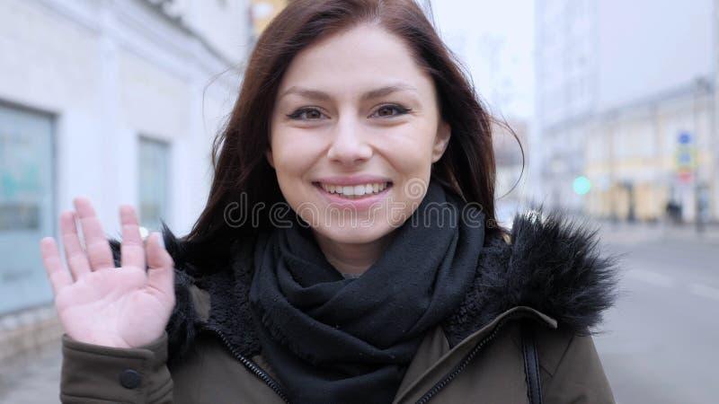 Hello-gebaar door jonge vrouw op straat, openlucht stock afbeelding