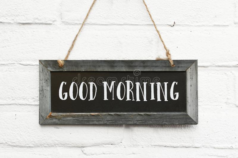 Hello good morning text on long hanging blackboard with wooden f royalty free stock photos
