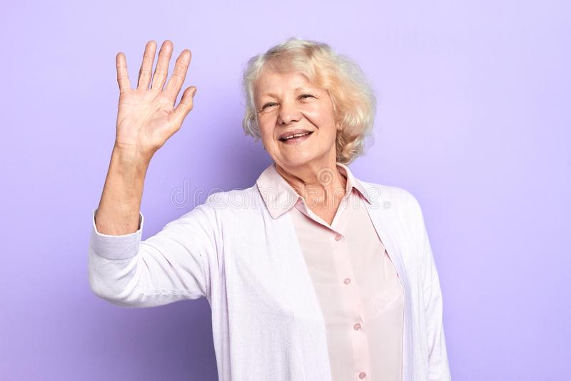Hello Happy stylish old woman raising her hand stock photos