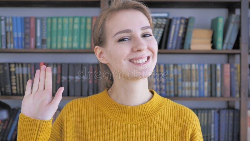 Hello, Jonge Vrouwen Golvende Hand aan Onthaal stock afbeelding