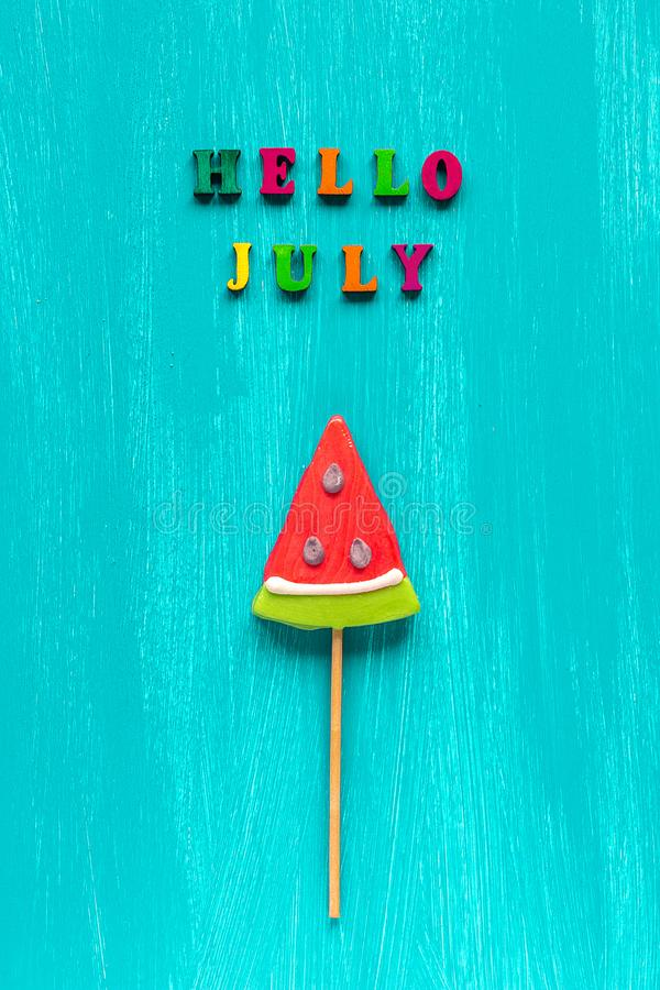 Hello July text from colorful letters and watermelon lollipop on stick on wooden blue background. Concept Creative Top royalty free stock photography