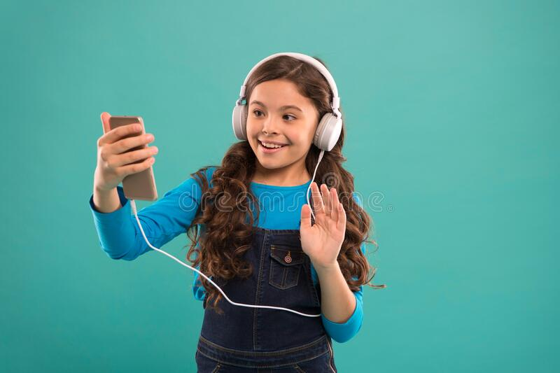 Hello. kid long hair make selfie in headset. small child make play list on smartphone. small girl use mp3 player. study royalty free stock image