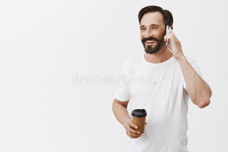 Hello kommer mig är över i kafé Glad och nöjd avkopplad man som har koppen kaffe och talar med vännen via smartphonen arkivbilder