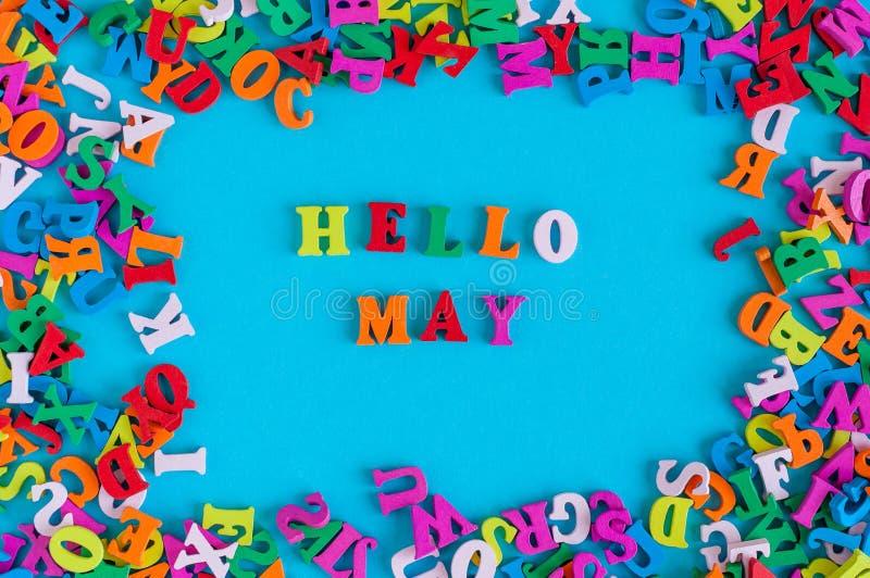 Hello Maj text på blå bakgrund i ram för många färgalfabetbokstäver arkivbild
