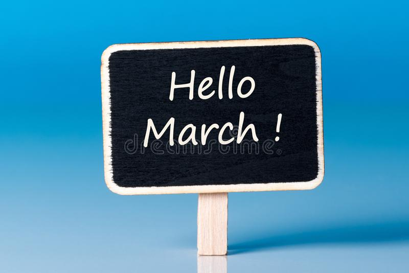 Hello March - inscription about spring beginning at litle wooden tag at blue background stock image
