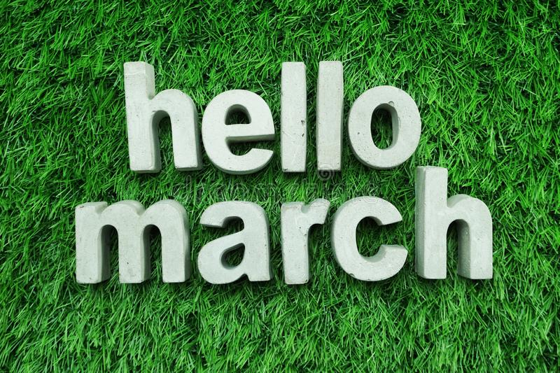 Hello March made from concrete alphabet on green grass. Hello March made from concrete alphabet top view on green grass royalty free stock image