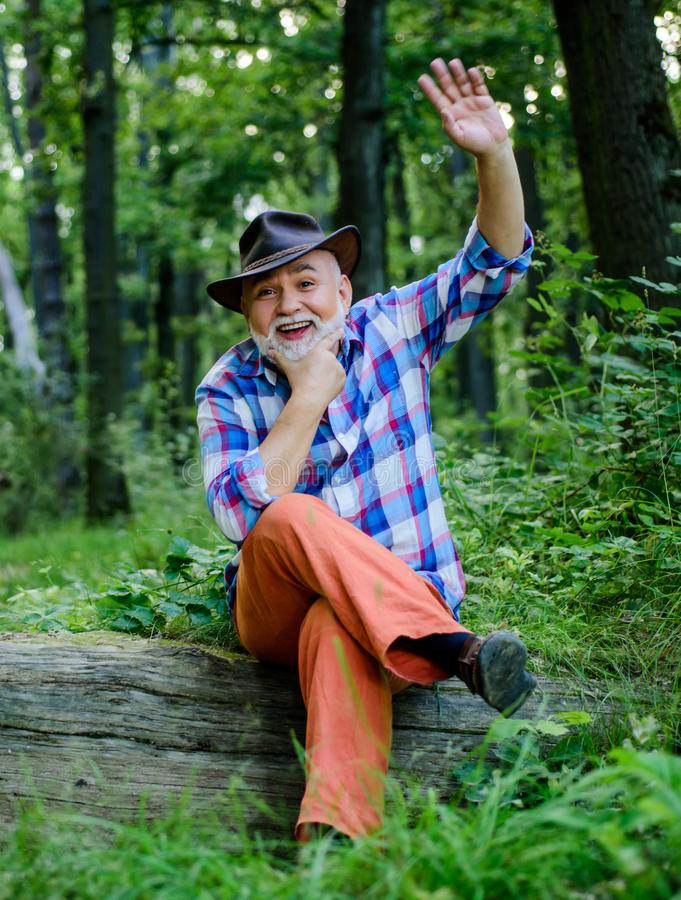 Hello. mature man with beard in cowboy hat. farmer sit on wood. happy forester. human and nature. hiking in deep wood royalty free stock photography