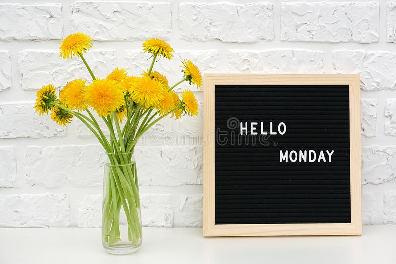 Hello Monday words on black letter board and bouquet of yellow dandelions flowers on table against white brick wall. Concept Happy royalty free stock photography