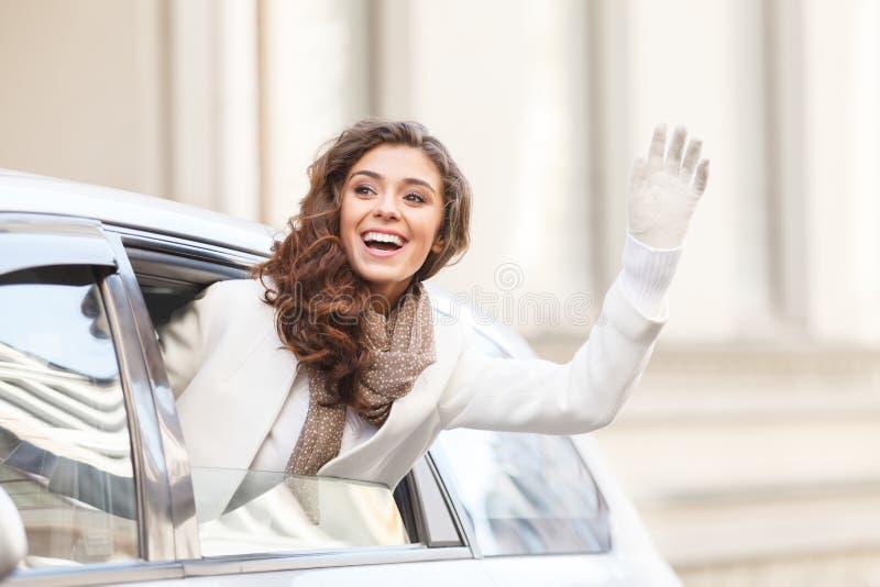 Hello! Mooie jonge vrouw die uit van een auto kijken die hello zeggen royalty-vrije stock foto's
