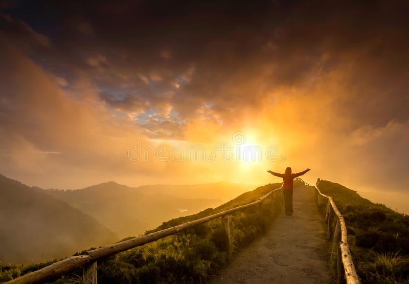 Hello Nature. Woman standing on a beautiful path with arms open at the sunset stock photos