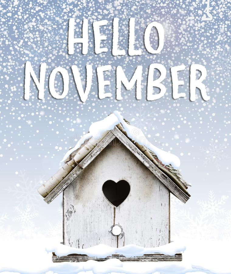 Hello November text winter snow falling down on cute little bird stock photo