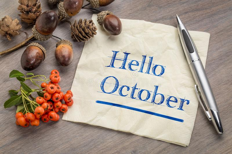 Hello October on napkin. Hello October handwriting on a napkin with cone, acorn and firethorn season decoration royalty free stock image