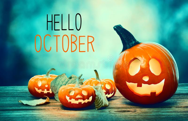Hello October with pumpkins at night. Hello October with pumpkins on a spooky forest at night royalty free stock photo