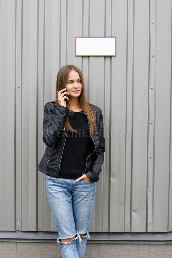 Hello. Outdoor summer closeup portrait of young stylish fashion glamorous brunette woman or girl posed in cloudy day jeans leather black jacket standing near royalty free stock image