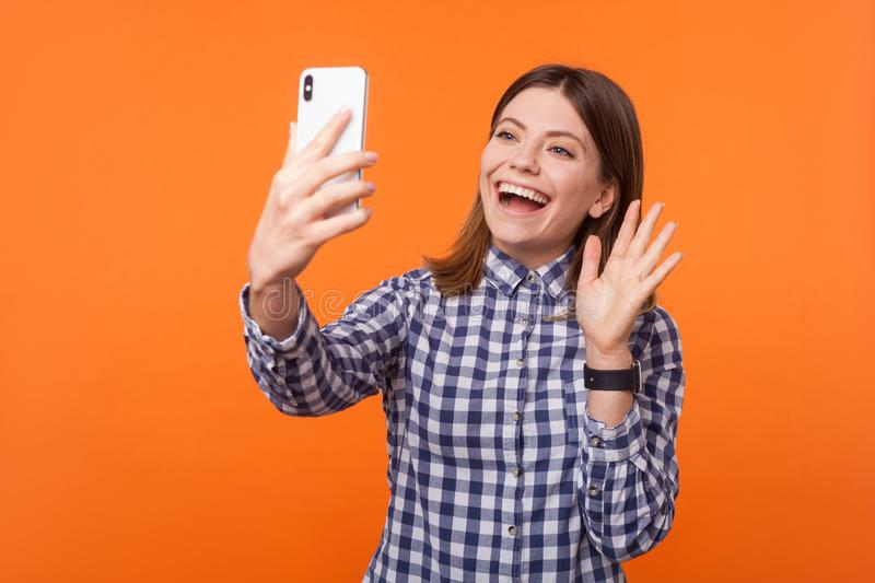 Hello! Portrait of adorable brunette woman with charming smile making video call. indoor studio shot isolated on orange background royalty free stock images