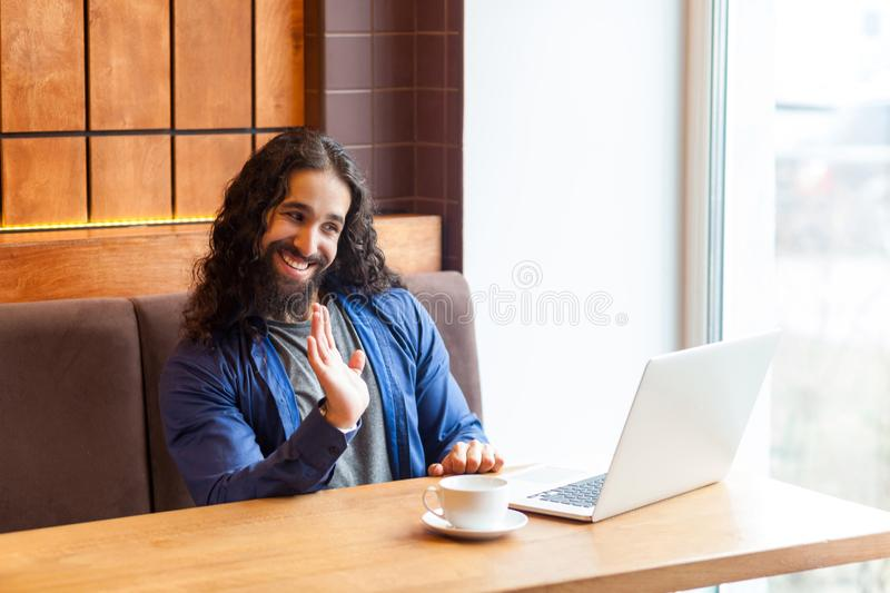 Hello! Portrait of glad handsome young adult man freelancer in casual style sitting in cafe and talking with his friend in laptop royalty free stock images